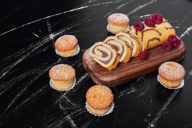 Rollkuchen mit beeren auf einer platte mit muffins.