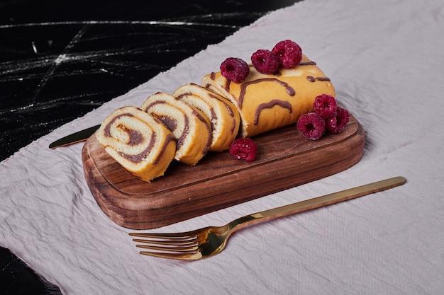 Rollkuchen mit himbeeren auf einer platte