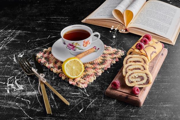 Rollkuchen mit schokolade und beeren und einer tasse tee.