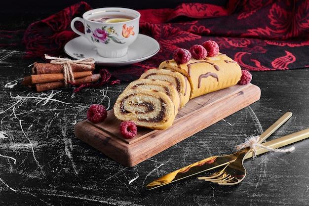Rollkuchen mit schokoladencreme und einer tasse tee.