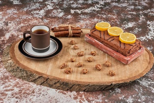 Rollkuchen und tee auf einem holzbrett.
