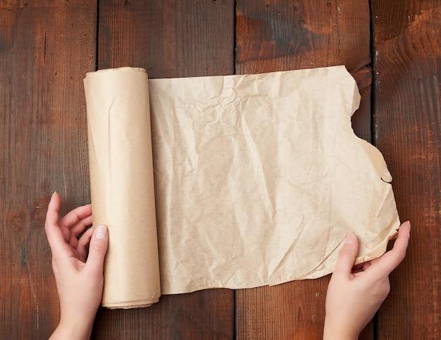 Rolls des braunen pergamentpapiers auf einer holzoberfläche
