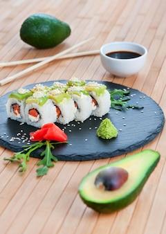 Rolls mit avocado auf einem bambushintergrund.