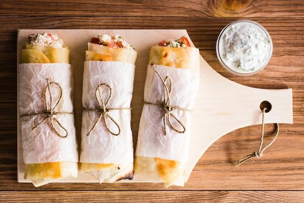 Rolls of pita mit füllung auf ein schneidebrett und sauce in der schüssel. ansicht von oben