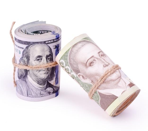Rolls von us-dollar und ukrainischen hryvnia-banknoten