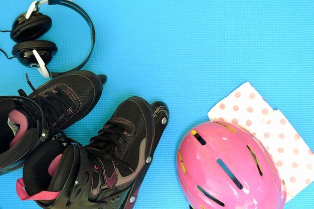 Rollschuhe mit rosa helm, schwarzes haupttelefon auf rückseite des blaus zurück für raum