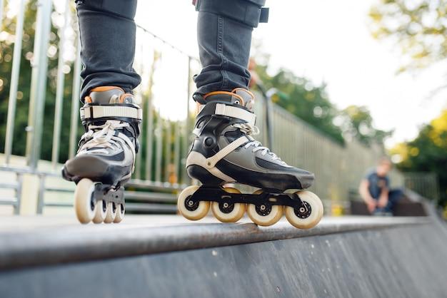 Rollschuhlaufen, männlicher skater stehend auf rampe. urbanes rollschuhlaufen, aktiver extremsport im freien