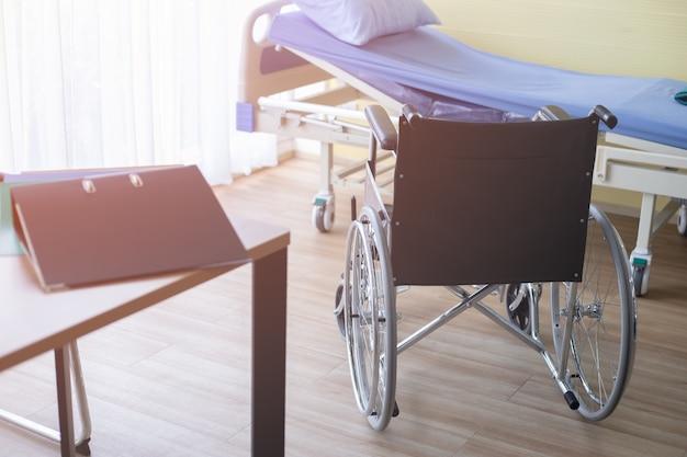 Rollstuhl und bett des geduldigen raumes im krankenhaus-, gesunden- und lebenkonzept