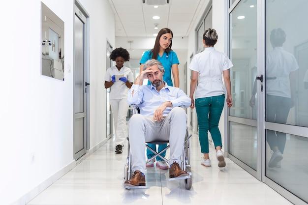 Rollstuhlpatientin mit professioneller ärztin und krankenschwester im korridor des krankenhauses