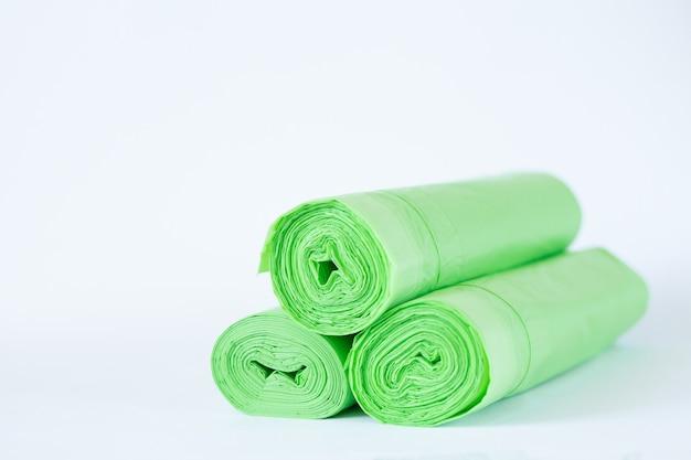 Rollt biologisch abbaubare grüne öko-plastikbeutel lokalisiert auf weißem hintergrund