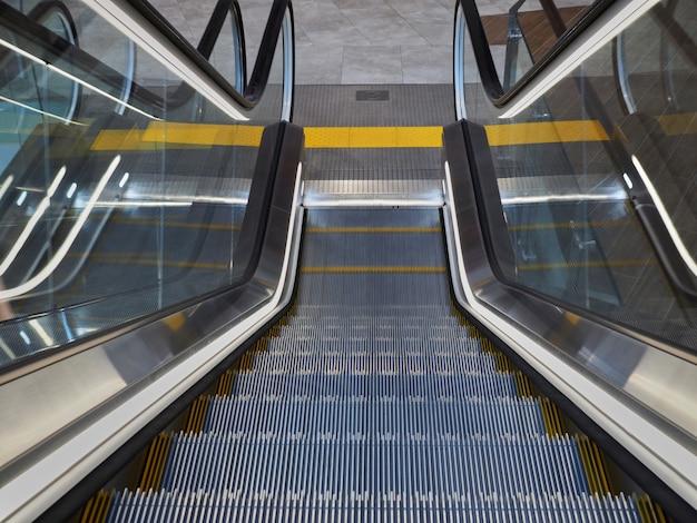 Rolltreppe im einkaufszentrum von oben mit gelbem streifen für blinde