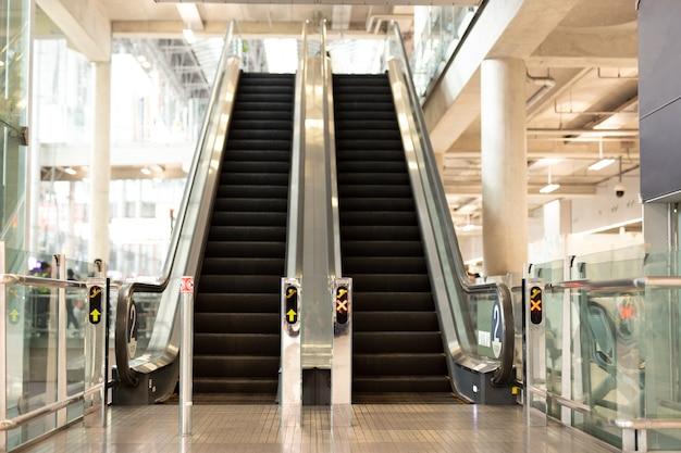 Rolltreppen, die in der hellen zeitgenössischen halle des modernen flughafens gelegen sind