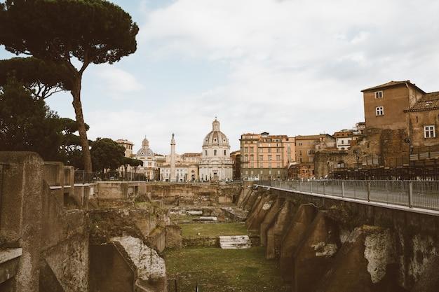 Rom, italien, 23. juni 2018: panoramablick auf das trajansforum und die säule in rom, weit weg von der kirche des allerheiligsten namens mariens. sommertag und blauer himmel