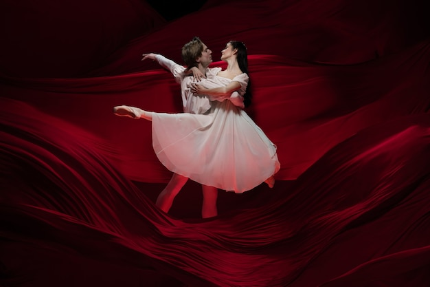 Roman. junge und anmutige balletttänzer auf roter stoffwand in klassischer aktion. kunst, bewegung, aktion, flexibilität, inspirationskonzept. flexibles kaukasisches paar mit wogenden roten wellen.