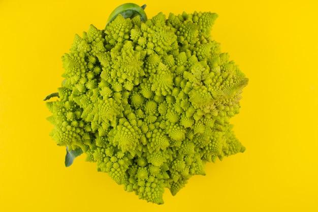 Romanesco-brokkoli (römischer blumenkohl) auf einem gelben hintergrund