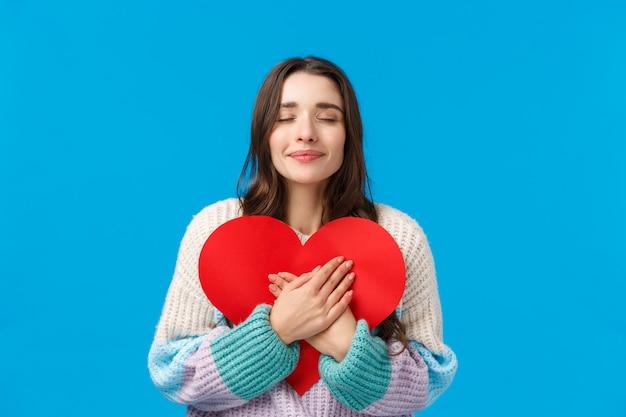 Romantik, beziehung und liebeskonzept. glückliche träumerische reizende brunettefreundin, die großes rotes pappherz, nahe augen und gefühlsneigung, sympathie für person umfasst, machte das geschenk, blau
