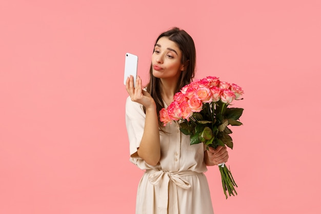 Romantik, beziehung und schönheitskonzept. zärtliches und albernes kokettes junges b-day-mädchen, das einen blumenstrauß erhält, möchte ein selfie mit blumen vom heimlichen bewunderer machen und den lippenstift auf dem handy überprüfen
