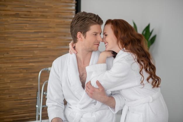Romantik. ein paar in weißen bademänteln umarmt und verliebt