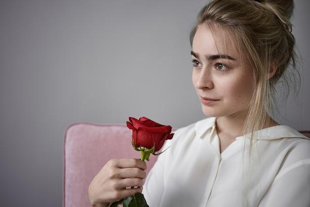 Romantik, liebe und natürliches schönheitskonzept. schließen sie herauf beschnittene ansicht der schönen romantischen jungen frau mit hellem haar, das weiße bluse trägt, die lokal sitzt und rote rose am valentinstag riecht
