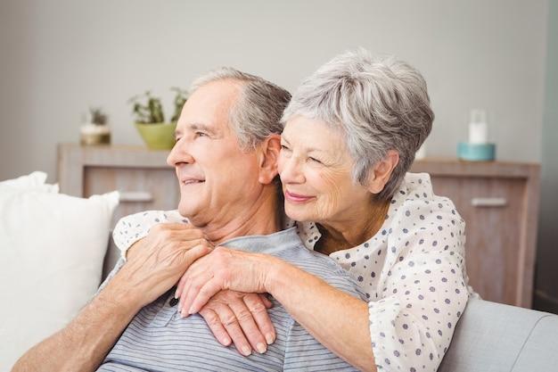 Romantische ältere paare, die im wohnzimmer sitzen