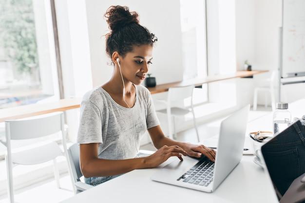 Romantische afrikanische frau mit trendiger frisur, die an ihrem arbeitsplatz sitzt und daten analysiert. innenporträt der schwarzen studentin, die mit laptop vor prüfung arbeitet.