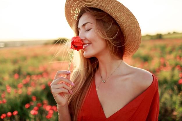 Romantische blonde frau mit blume in der hand, die in erstaunlichem mohnfeld geht. warme sonnenuntergangsfarben. strohhut. rotes kleid. weiche farben.