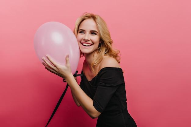 Romantische blondhaarige frau mit großem lächeln, das im schwarzen kleid auf hellrosa wand aufwirft. charmantes geburtstagskind mit heliumballon.