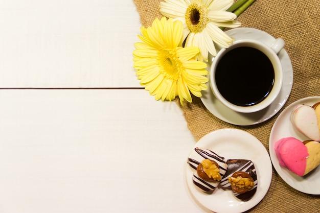 Romantische blumen mit kaffee und süßen festlichkeiten auf dem tisch