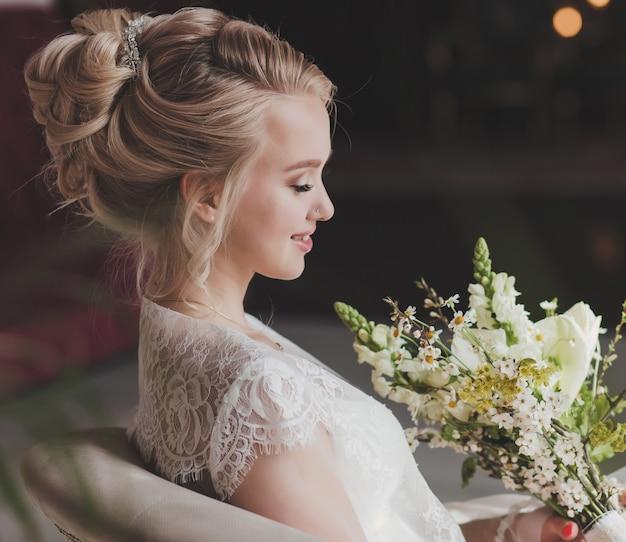 Romantische braut mit frisur und make-up, die auf stuhl im studioraum sitzt