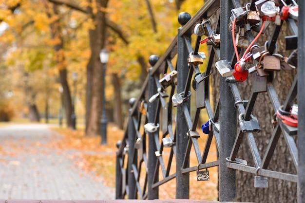 Romantische brücke mit verschlüssen von leuten in der liebe im herbstpark