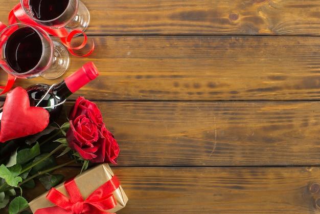 Romantische dekoration des valentinsgrußtages mit rosen, wein und geschenkbox auf einem braunen holztisch