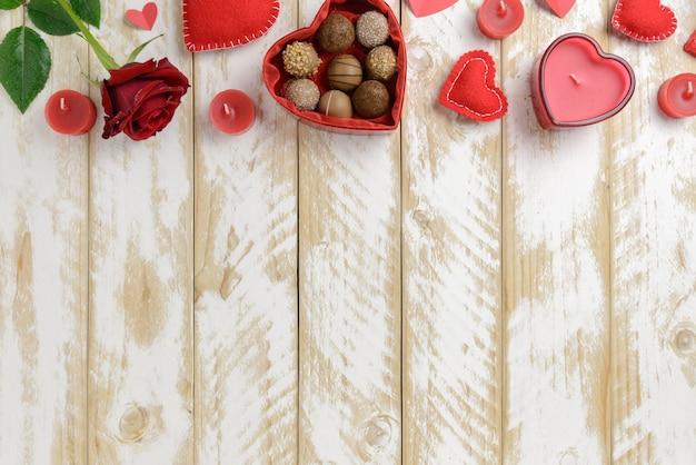 Romantische dekoration des valentinstags mit rosen und schokolade auf einem weißen holztischhintergrund
