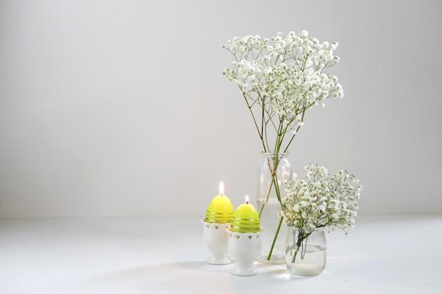 Romantische elegante blumensträuße mit weißen blumen gipsophyla und kerzen auf weißem hintergrund. speicherplatz kopieren. osterkonzept.