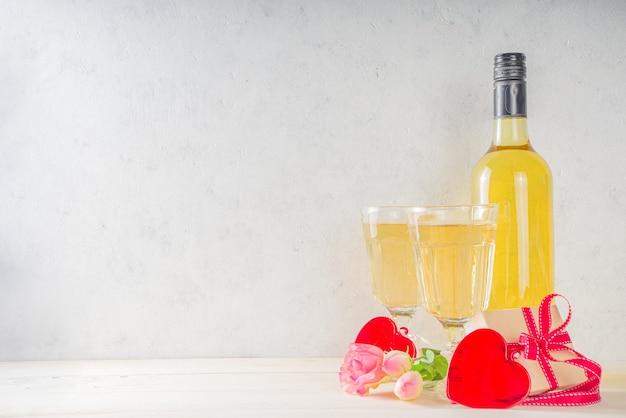 Romantische feier des valentinstags. zwei weißweingläser mit roten herzen und rosen. auf weißem hintergrund kopierraum