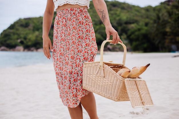 Romantische frau am strand im rock gestricktes oberteil und strohhut, die korb mit brot eco leben halten