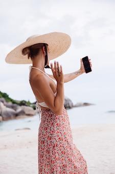 Romantische frau am strand im rockstrickoberteil und im strohhut
