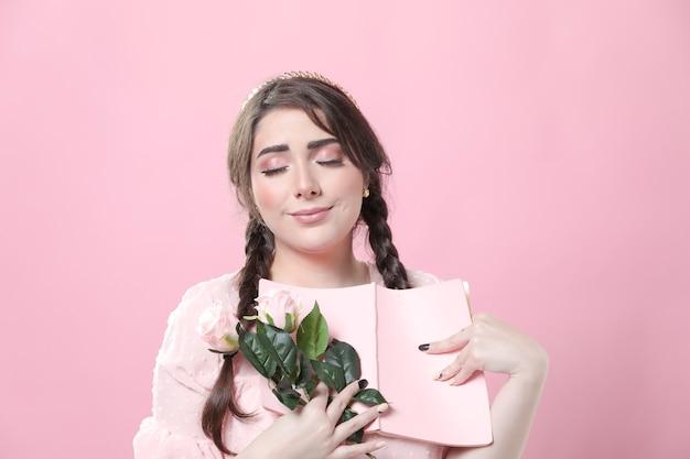 Romantische frau, die rosen und buch hält