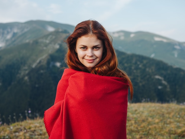Romantische frau, die sich hinter einem roten plaid in den bergen draußen in der natur versteckt.