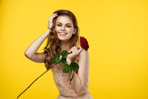 Romantische frau im abendkleid mit roter rose auf gelbem hintergrund beschnittenes ansichtsporträt.