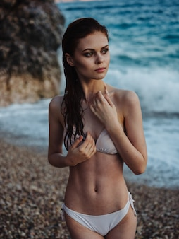 Romantische frau im badeanzug rockt naturinselozean. hochwertiges foto