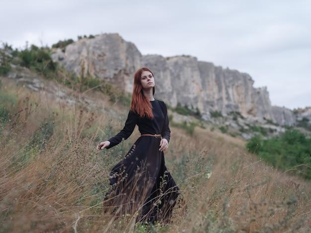 Romantische frau im schwarzen kleid, das in der natur in den bergen hübsche frau ruht