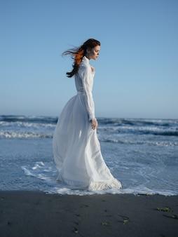 Romantische frau im sommerkleid in voller länge am strand des blauen himmels des ozeans