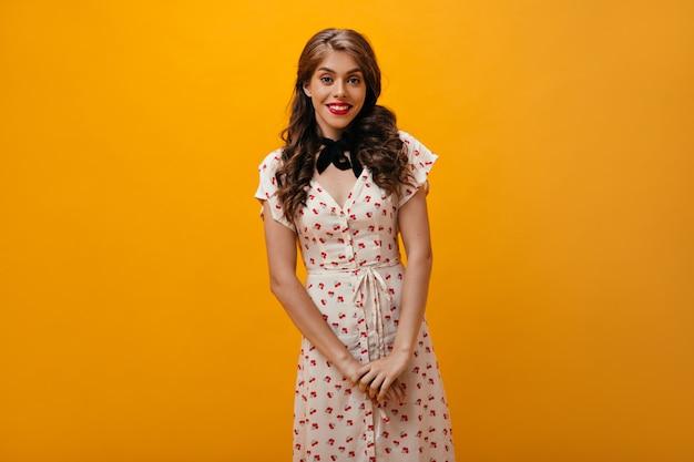 Romantische frau im weißen kleid wirft auf orange hintergrund auf. schönes mädchen mit welligem haar im modernen outfit, das in die kamera schaut.