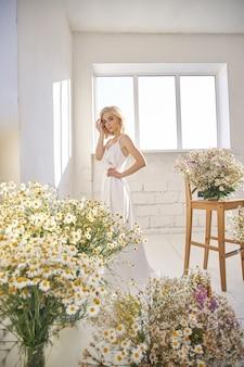 Romantische frau in einem langen weißen hochzeitskleid steht nahe am fenster in kamillenblüten