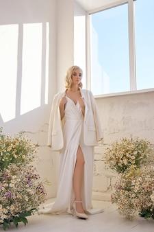 Romantische frau in einer jacke und einem langen weißen kleid steht in kamillenblüten am fenster