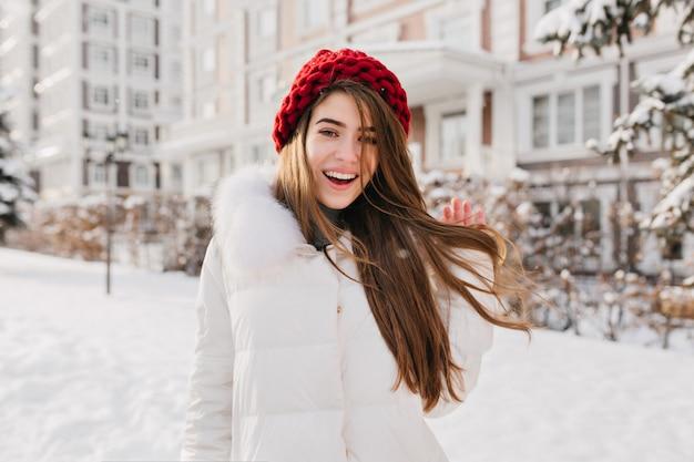 Romantische frau in roter strickmütze spielt mit ihren langen braunen haaren in der verschneiten straße. foto im freien des begeisterten europäischen weiblichen modells, das in den winterferien herumläuft.