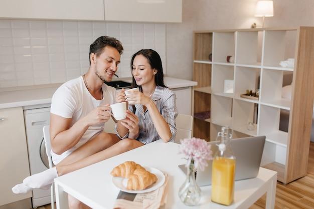 Romantische frau in weißen socken, die mit ehemann während des frühstücks chillen und croissants genießen