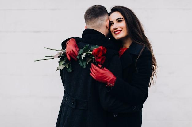 Romantische frau mit blumen, die mann umfassen