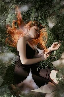 Romantische frau mit dem roten haar, das im gras liegt