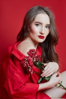 Romantische frau mit langen blonden haaren im roten kleid